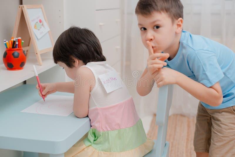 Brat wtyka papierowej ryby plecy siostry na Kwietnia durnia dniu Dziecko humor na Kwietniu 1 Dowcipy i zabawa obrazy stock