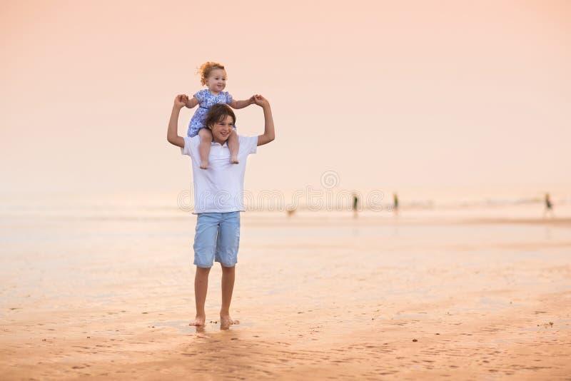 Brata i dziecka siostra bawić się na pięknej plaży przy zmierzchem obrazy royalty free