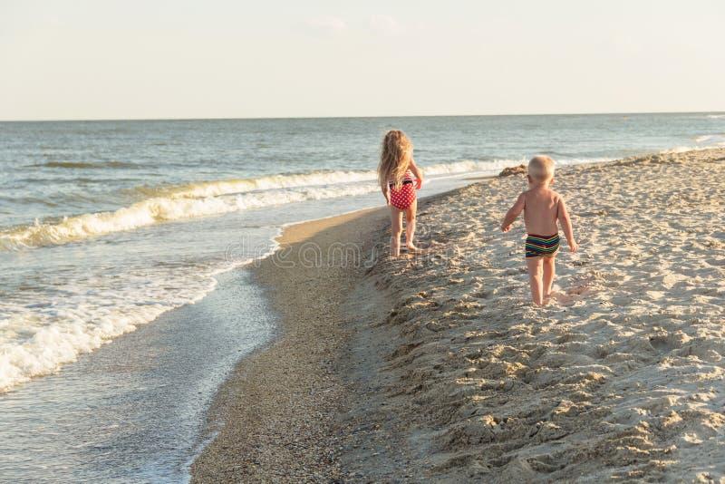 Brata i siostry bieg na piasku pogodna plaża obraz stock