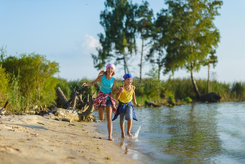 Brata i siostry bieg wzdłuż plaży Wakacje i podróży pojęcie zdjęcia royalty free
