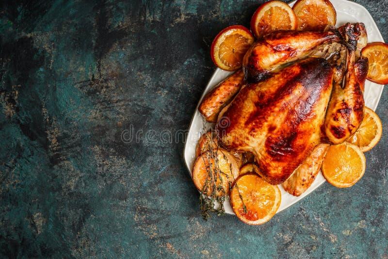 Braten Sie ganzen Truthahn oder Huhn in der Platte mit gebratenen Orangen auf dunklem rustikalem Hintergrund lizenzfreie stockfotos