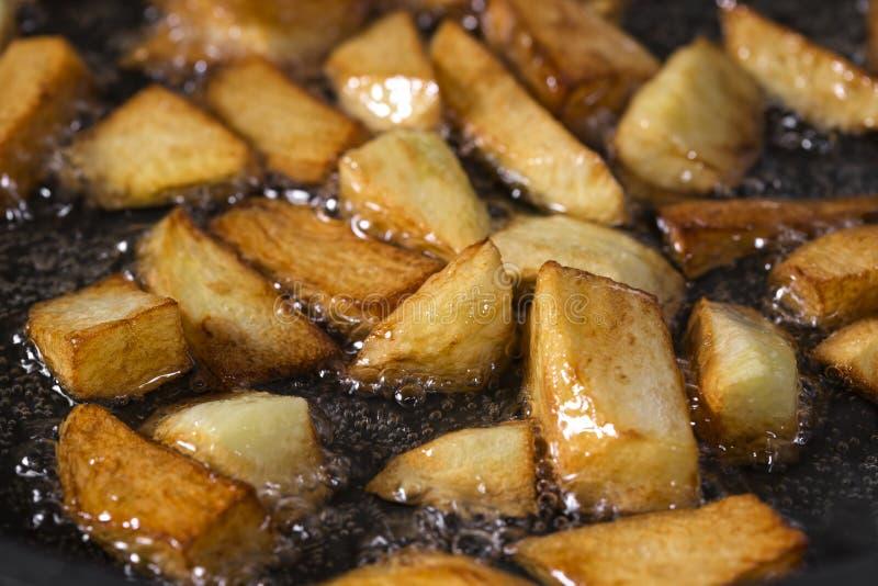 Braten von frischen rohen gehackten Kartoffeln im Pan With Hot-Sonnenblumenöl lizenzfreie stockfotografie