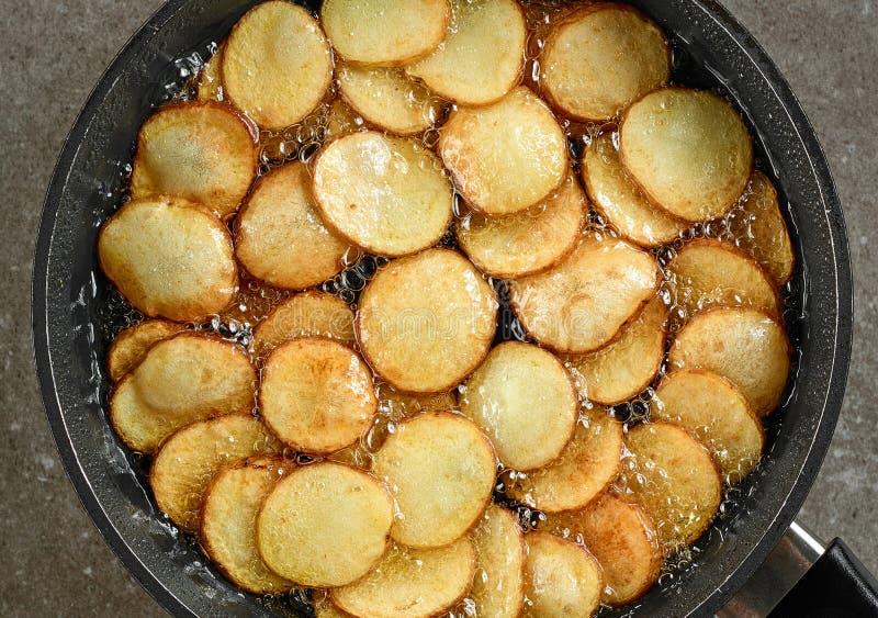 Braten von Kartoffeln in der Wanne mit Öl stockbild