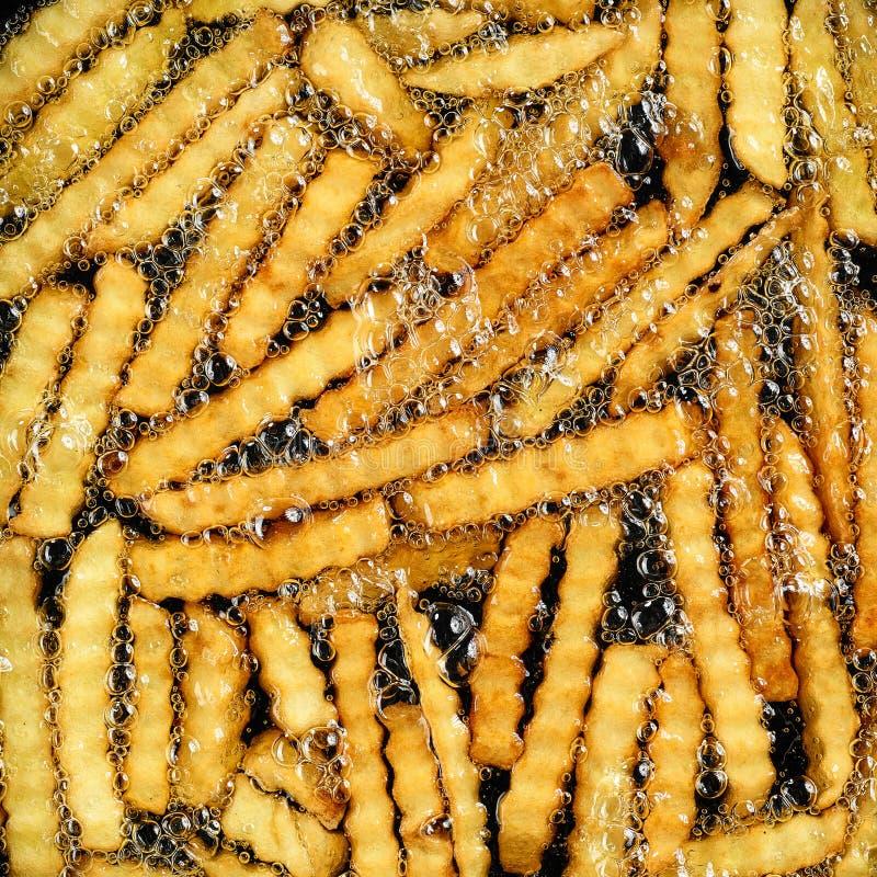 Braten von Kartoffeln im Heißöl stockfoto
