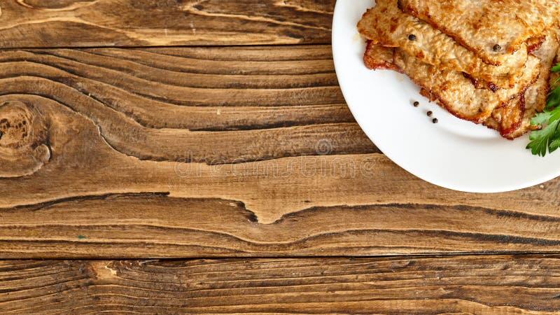 Bratenfleisch in einer Platte auf einem Holztisch Geschossen von oben stockfotografie