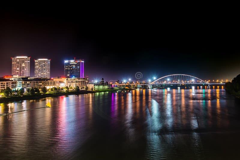 Bratislava en la noche, con las luces de la ciudad reflejadas en el río Danubio foto de archivo