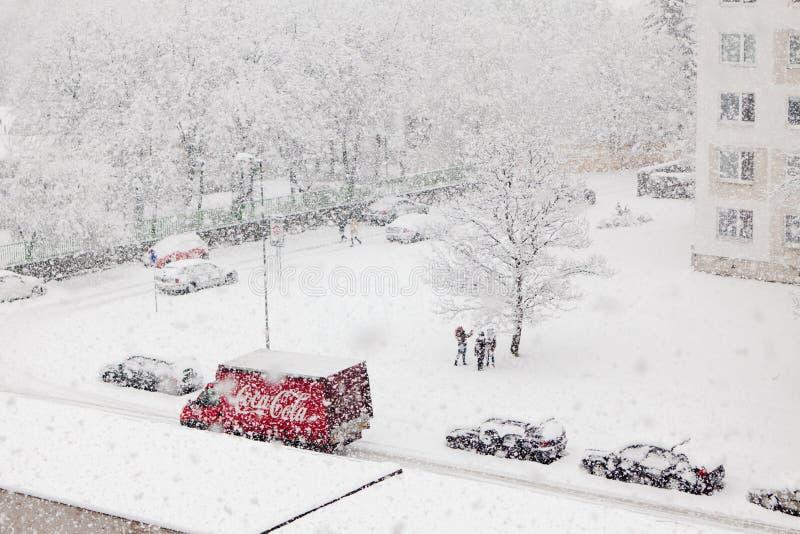 Bratislava, Eslováquia, 30o Em janeiro de 2015: Carro de entrega vermelho da coca-cola em nevar pesado - as crianças apreciam a imagens de stock