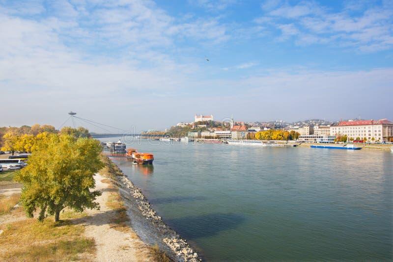 BRATISLAVA, ESLOVAQUIA, OCTUBRE - 27, 2016: El panorama con el puente, la costa, la catedral y el castillo de SNP imagen de archivo libre de regalías