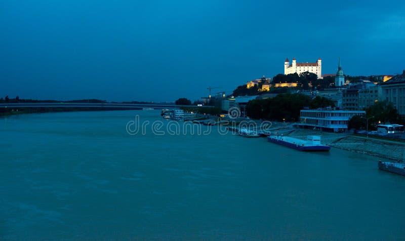 Bratislava slott ovanför Danube River på skymning arkivbild