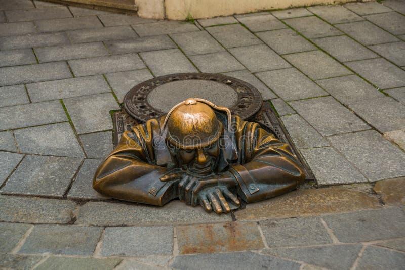 BRATISLAVA, SLOWAKEI: Bronzeskulptur des Klempners in Bratislava Statuen-Herr Cumil Der Beobachter oder der Mann bei der Arbeit lizenzfreies stockbild