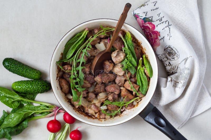 Bratpfanne des gebratenen Fleisches mit Grüns und Zwiebeln gulasch Nahe frischen Gurken, Rettichen und Spinat stockfotografie