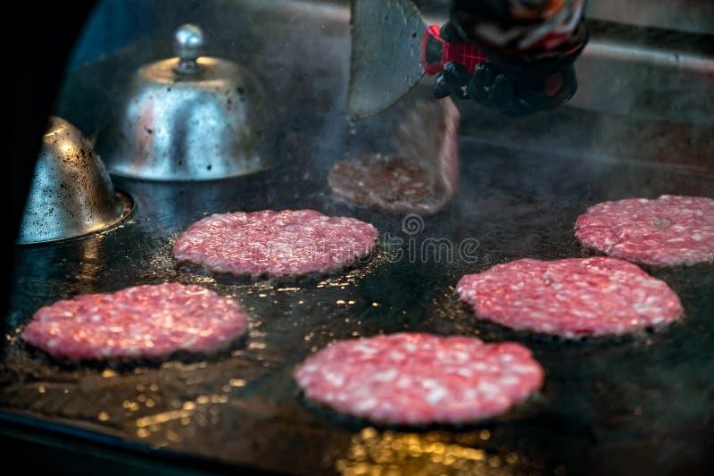 Bratrohe gemarmorte Rindfleisch-Burgerpastetchen auf Eisengrill lizenzfreie stockfotografie