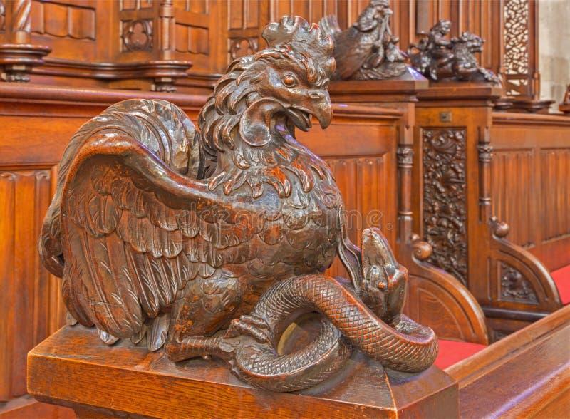 Bratsilava - symbolisk sniden skulptur för hane och för orm från bänk i presbyterium av St.-morgonböndomkyrkan royaltyfri bild