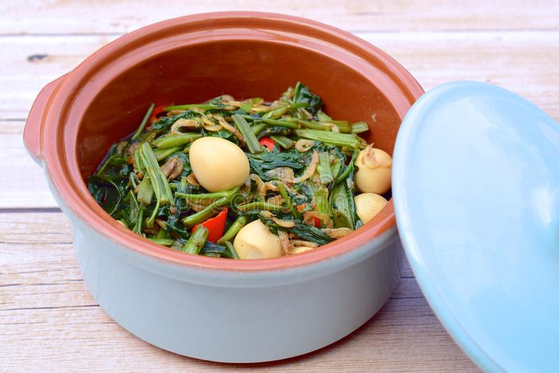 Bratspinat oder Kangkung mit gebratenen Sardellen und Eiern aus Wachteln Eine der berühmten indonesischen Spezialitäten stockbilder