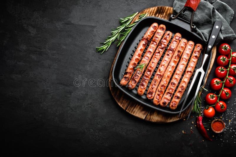 Bratwurst grelhada das salsichas na frigideira da grade no fundo preto Vista superior Culinária alemão tradicional fotografia de stock royalty free