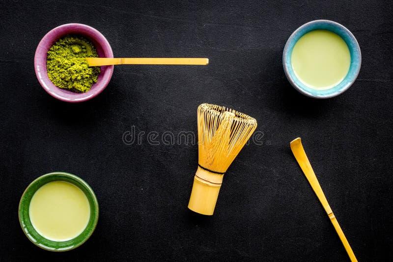 Brauen Sie matcha grünen Tee Matcha-Pulver, bereiter matcha Tee, Schneebesen auf Draufsicht des schwarzen Hintergrundes stockbild