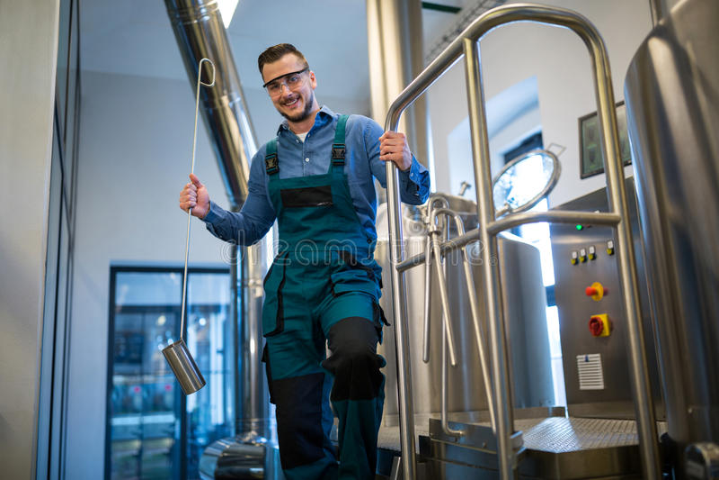 Brauer, der Arbeitsausrüstung an der Brauerei hält stockfotografie