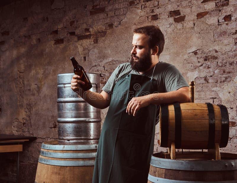 Brauer im Schutzblech, das nahe Fässer steht und Getränke machen Bier an der alten Brauereifabrik in Handarbeit lizenzfreie stockfotos