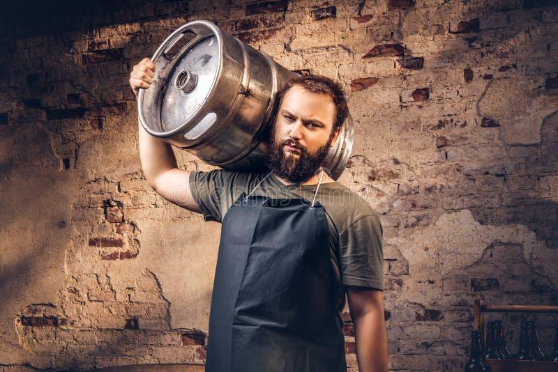 Brauer im Schutzblech hält Fass mit Handwerksbier an der Brauereifabrik lizenzfreies stockbild