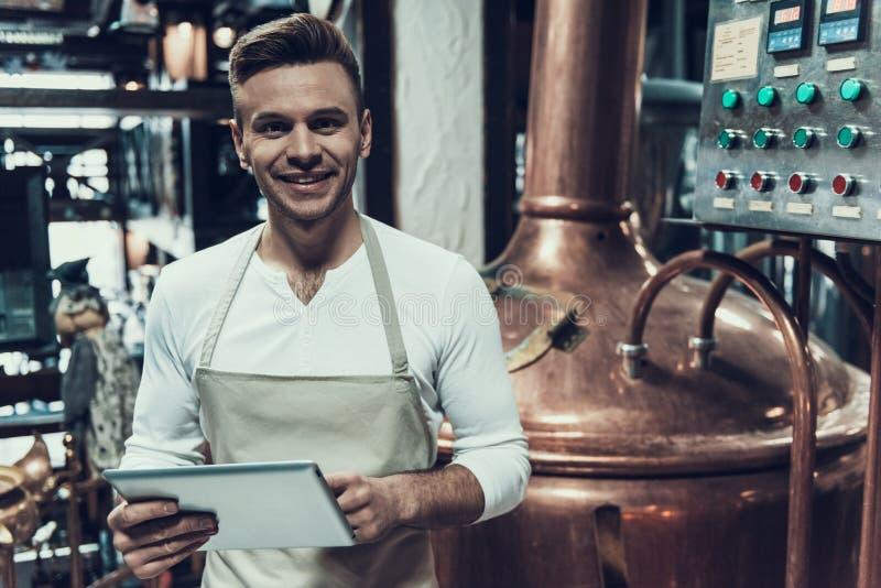 Brauer Standing nahe Apparat in der modernen Brauerei lizenzfreies stockfoto