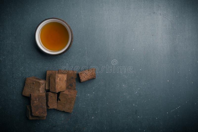braune Eibisch- und Teeschale auf dunklem Hintergrund stockbild