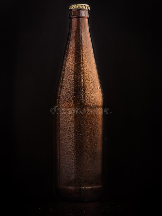 Braune Flasche des Bieres auf schwarzem Hintergrund stockbild