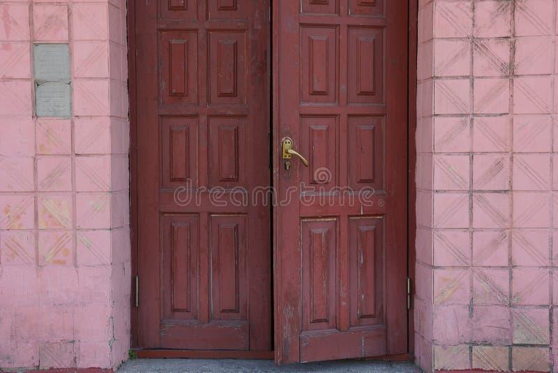braune Holztür auf einer schmutzigen roten Fliesenwand stockfotos