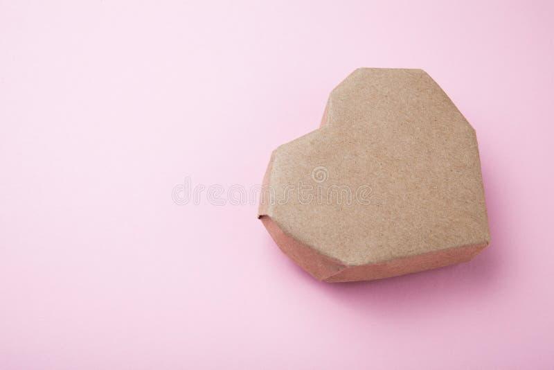 Braunes Papierherz auf einem rosa Hintergrund Kopieren Sie Raum f?r Text stockfotos