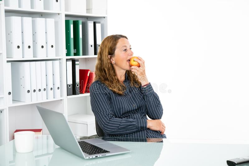 Braunhaarige blonde Geschäftsfrau, die Apfel isst lizenzfreie stockfotografie