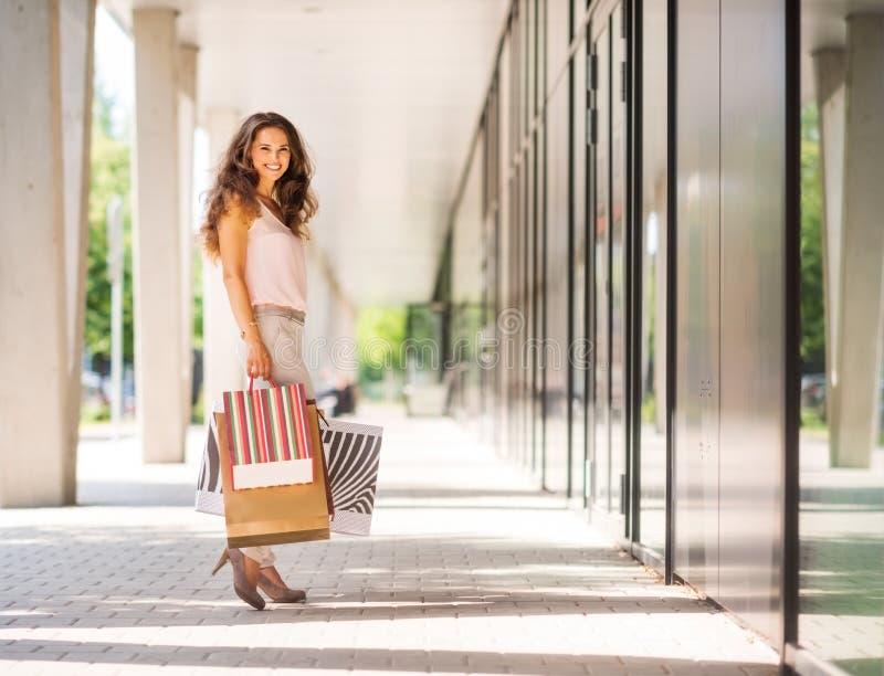 Braunhaarige Frau, die bunte Einkaufstaschen halten lächelt lizenzfreies stockbild