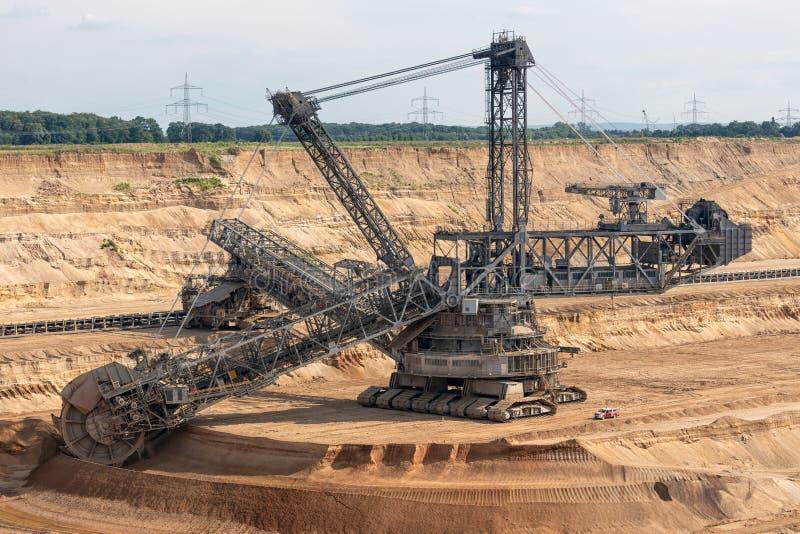 Braunkohle-Tagebaulandschaft mit grabendem Bagger in Deutschland lizenzfreie stockfotos