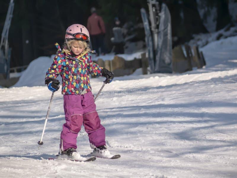 Braunlage, Deutschland - 15 Februar 2015: Wintersportfeiertag für die Familie Kleines Mädchen, das abwärts Ski fährt Winterfamili lizenzfreies stockfoto
