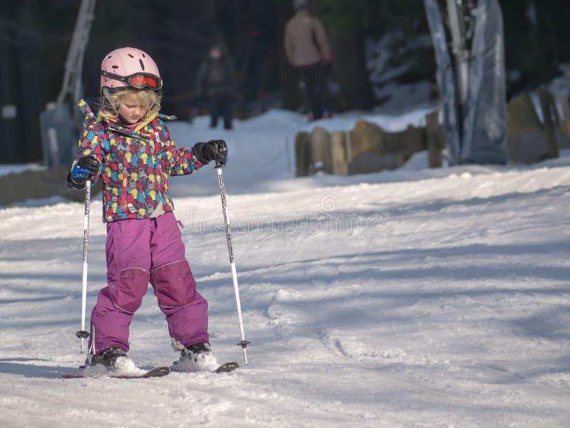 Braunlage, Deutschland - 15 Februar 2015: Wintersportfeiertag für die Familie Kleines Mädchen, das abwärts Ski fährt Winterkind-` stockfoto