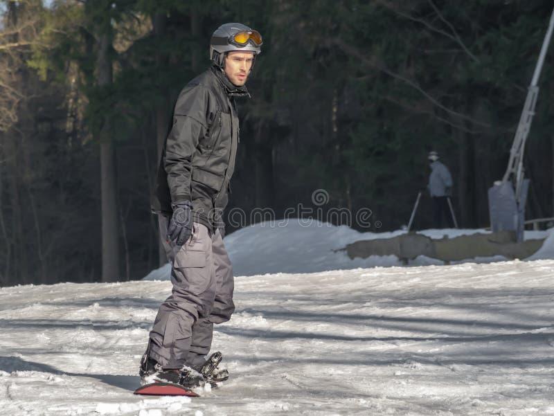 Braunlage Tyskland - 15 Februar 2015: Vintersportlov för familjen Den unga mannen i hjälm, med skyddsglasögon, skidar in dräkten  fotografering för bildbyråer