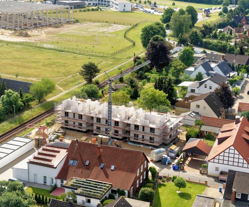 Braunschweig lägre Sachsen, Tyskland, Maj 24, 2018: Konstruktionsplatsen för en hyreshus på kanten av en förort, antenn tävlar arkivbild