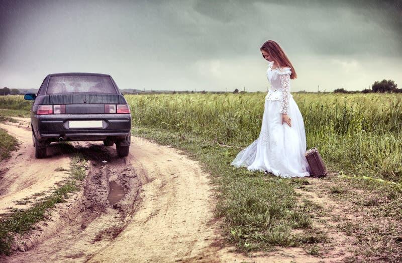 Braut auf der landwirtschaftlichen Straße mit einem alten Koffer stockbilder