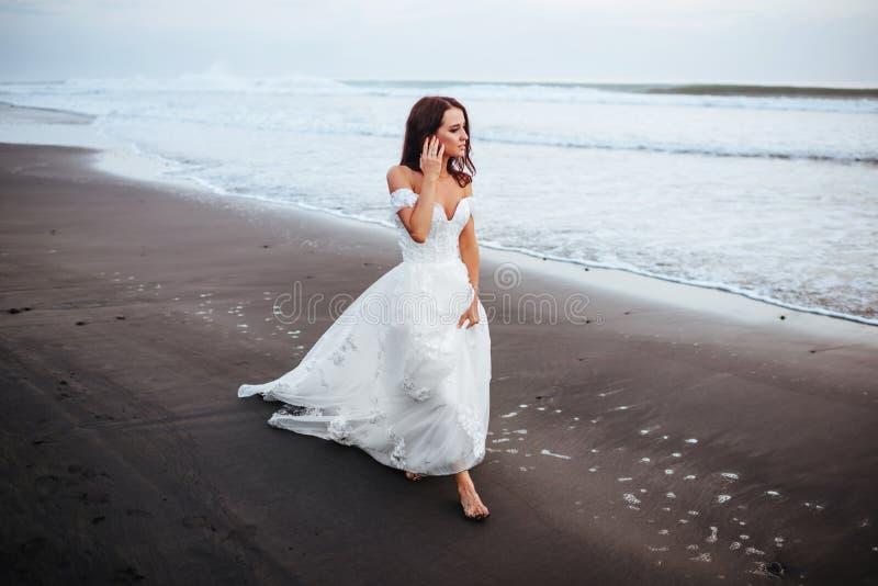 Braut auf einem Strand im blauen Wasser lizenzfreies stockfoto
