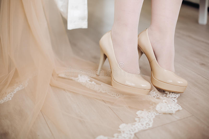 Braut beschuht weißen Hochzeitsschleier auf dem Boden mit Spitze stockbild