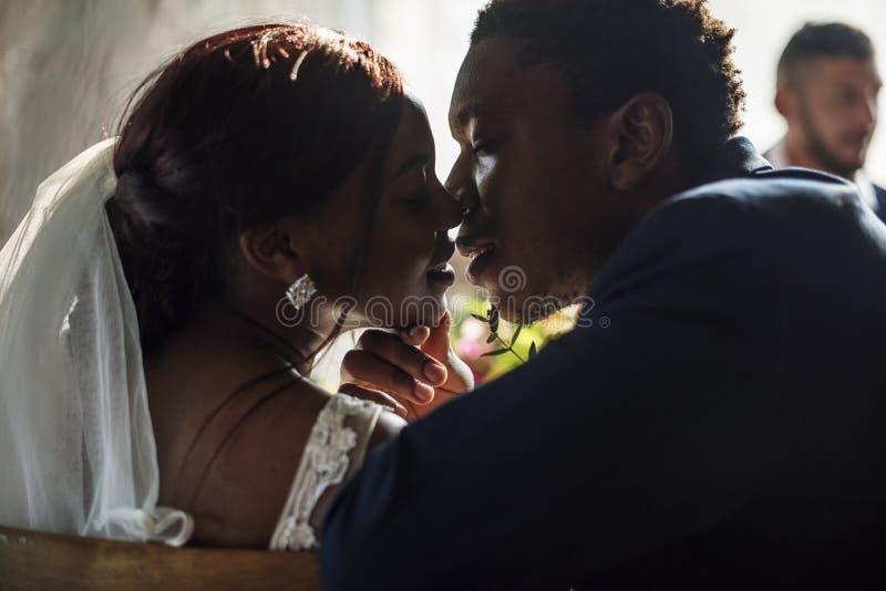 Braut der Jungvermählten-afrikanischen Abstammung, die Bräutigam Wedding Celebration küsst stockbild
