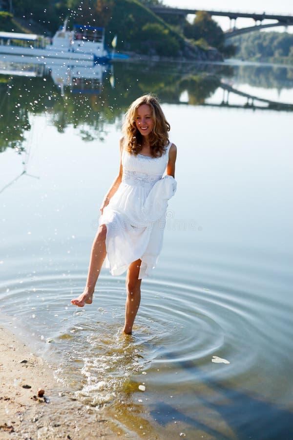 Braut des jungen Mädchens, die Spaß auf dem Spritzwasser im Fluss hat lizenzfreie stockfotos