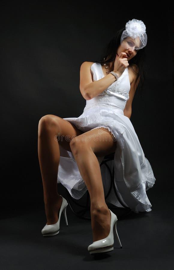 Braut, die auf dem Stuhl stillsteht. lizenzfreie stockbilder