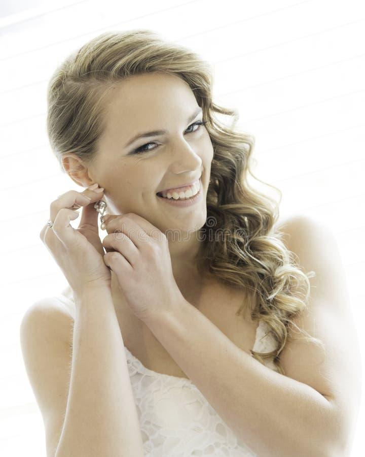 Braut, die auf Ohrring sich setzt stockbilder