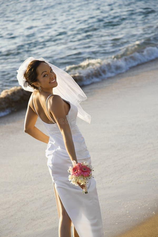 Braut, die auf Strand steht. lizenzfreie stockfotografie