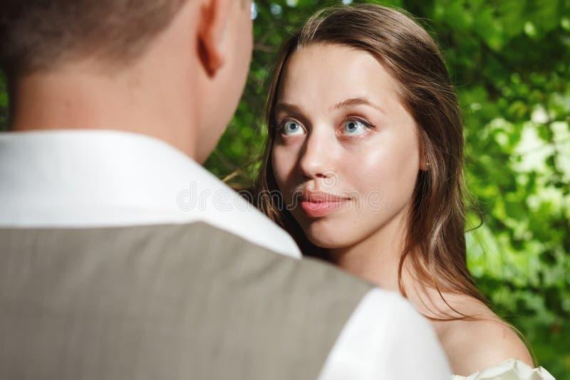 Braut, die Bräutigam mit Liebe und Angebot betrachtet stockfotos