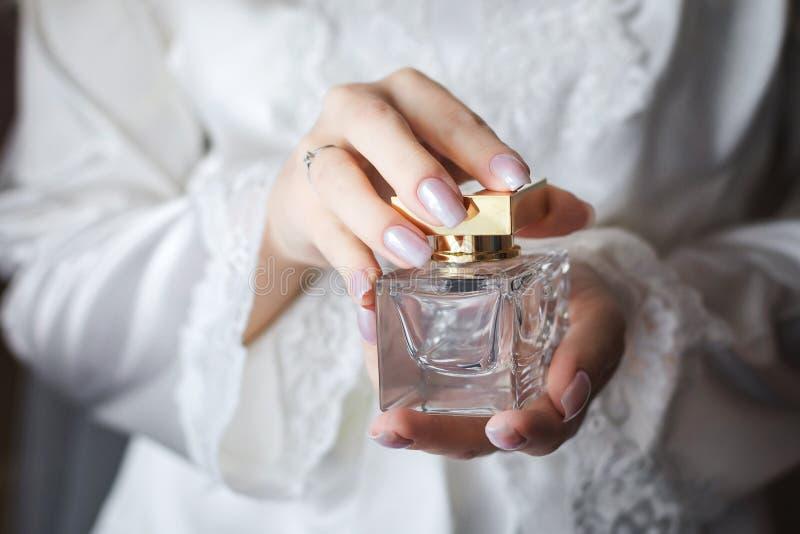 Braut, die in den Händen ein flacon des Luxusparfüms hält lizenzfreies stockbild