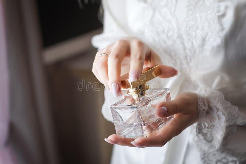 Braut, die ein flacon eines wohlriechenden Parfüms öffnet lizenzfreies stockfoto