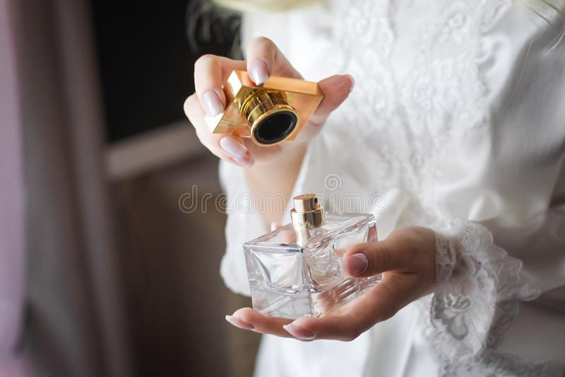 Braut, die eine Flasche Luxusparfüm öffnet lizenzfreies stockfoto