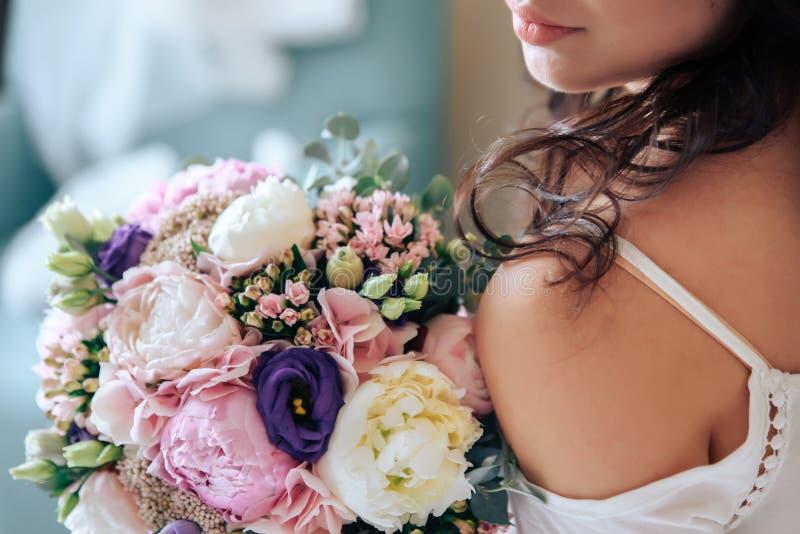 Braut, die einen Blumenstrauß von Blumen in der rustikalen Art, heiratend hält lizenzfreie stockbilder