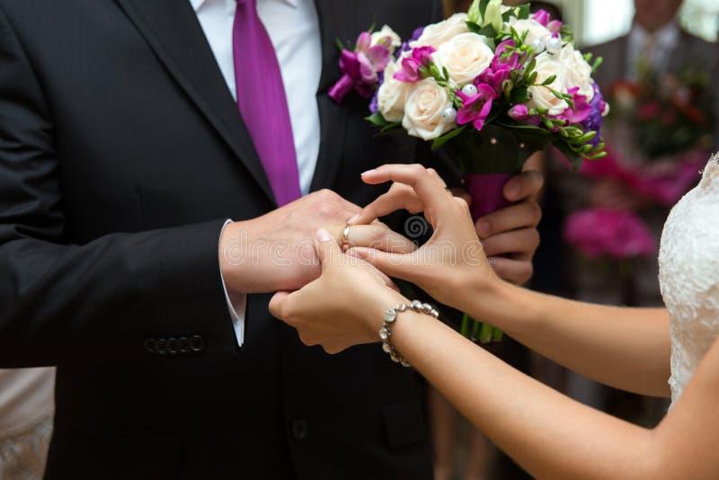 Braut, die einen Ring auf den Finger des Bräutigams setzt lizenzfreies stockfoto