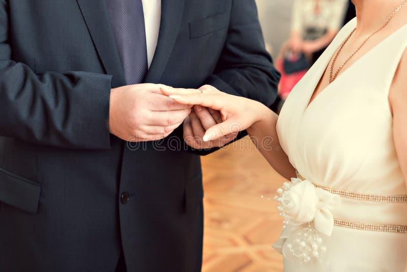 Braut, die einen Ring auf den Finger des Bräutigams setzt lizenzfreies stockbild